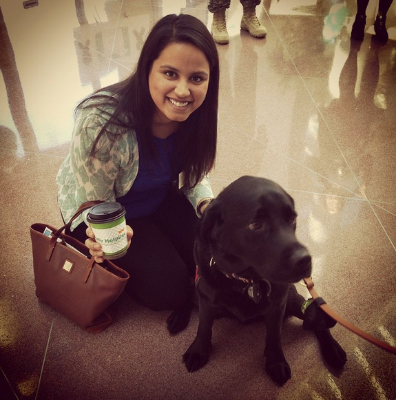 RAINN staffer Kinjal Dalal poses with a dog and a coffee cup with a DoD Safe Helpline sleeve.