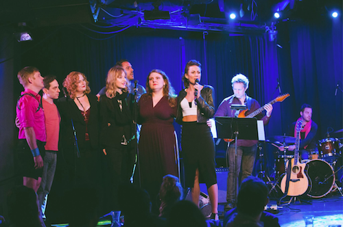 Six Broadway stars gather on stage to sing with a band playing on stage behind them