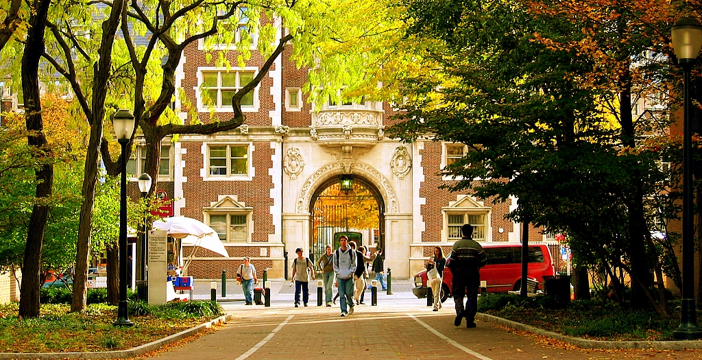 Students walk under an archway on a college campus in the fall.