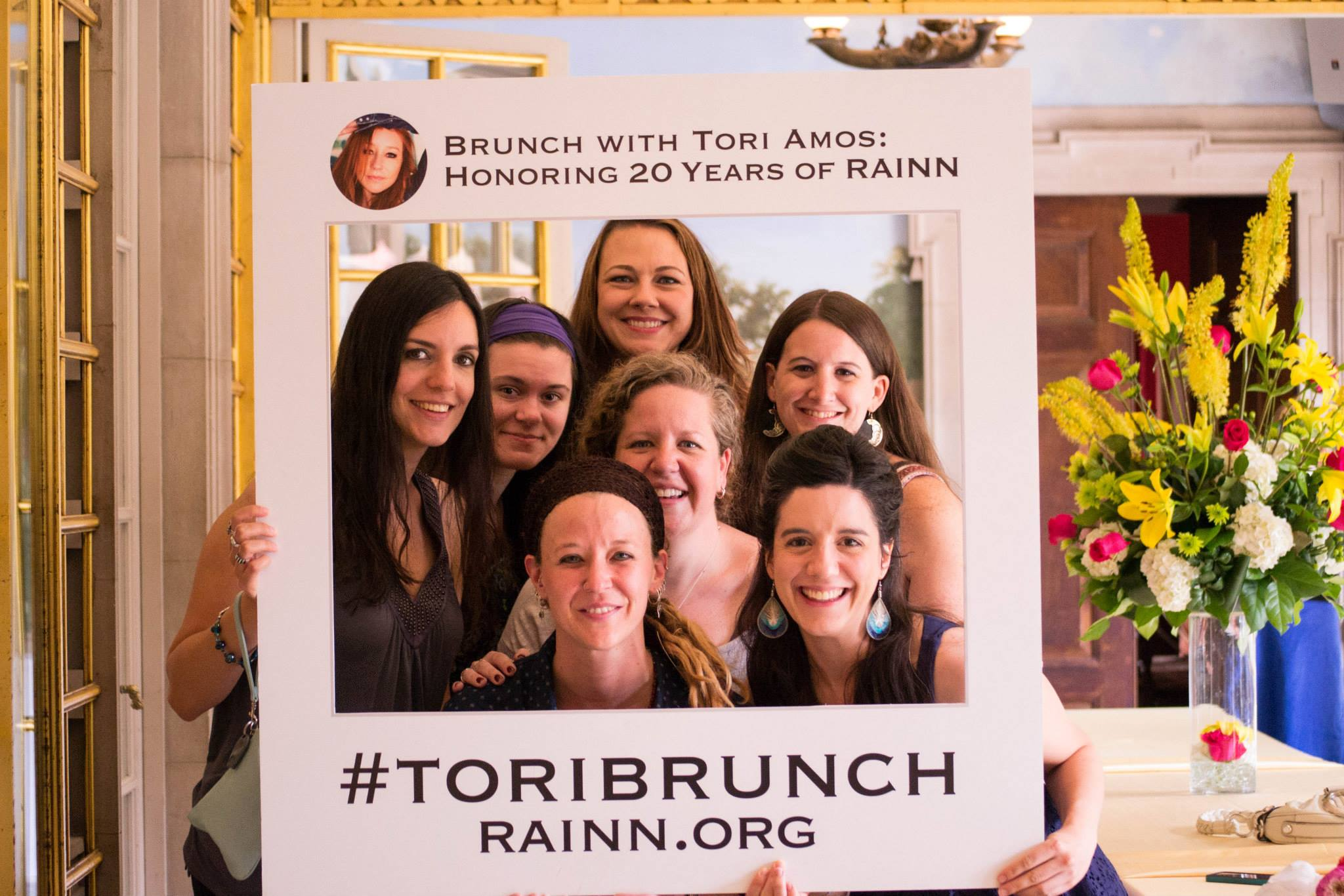 "Women pose with a sign stating ""Brunch with Tori Amos: Honoring 20 years of RAINN, hashtag ToriBrunch, rainn.org"""
