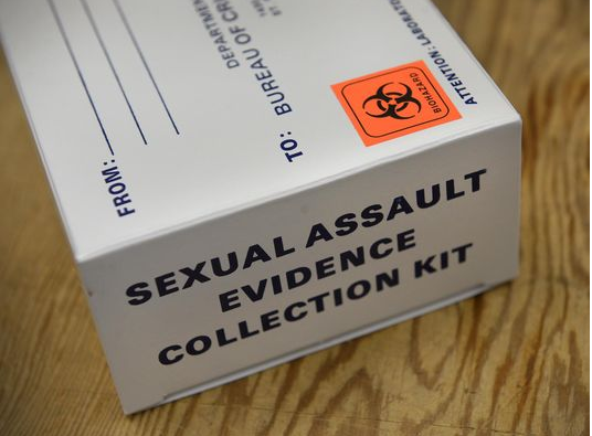 "White box with an orange biohazard sticker and a label that reads ""Sexual assault evidence collection kit."""