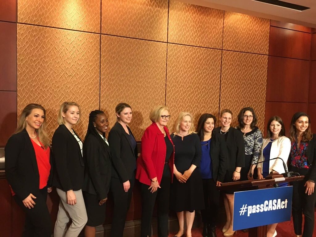 "Members of congress, RAINN staff, and other anti-sexual assault advocates pose behind a podium. The podium holds a sign reading ""Pass CASA act."""